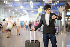 Jonge Aziatische mens die op de vlucht in luchthaven wachten Royalty-vrije Stock Afbeeldingen