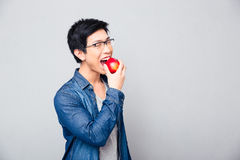 Jonge Aziatische mens die rode appel bitting Royalty-vrije Stock Foto's