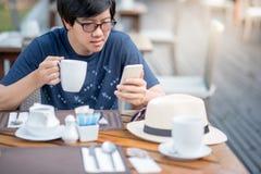 Jonge Aziatische mens die slimme telefoon met behulp van tijdens het hebben van ontbijt Stock Foto's