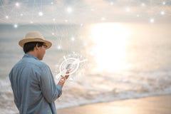 Jonge Aziatische mens die smartphone op het strand gebruiken royalty-vrije stock afbeeldingen