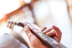 Jonge Aziatische mens die Spaanse gitaar binnen spelen stock foto's
