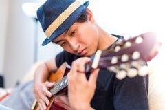 Jonge Aziatische mens die Spaanse gitaar binnen spelen stock afbeelding