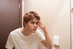 Jonge Aziatische mens die in spiegel kijken en zijn huid in bathr controleren royalty-vrije stock fotografie