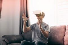 Jonge Aziatische mens die virtuele werkelijkheidsglazen dragen bij woonkamer voor het bewonderen van virtuele werkelijkheid royalty-vrije stock fotografie