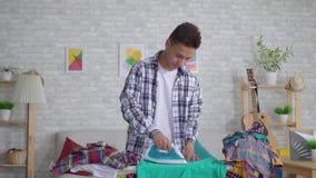 Jonge Aziatische mens het strijken kleren op strijkplank dicht omhoog langzame mo stock videobeelden