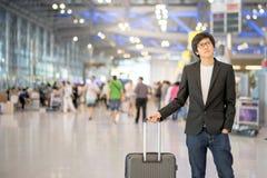Jonge Aziatische mens met bagage in luchthaventerminal Royalty-vrije Stock Afbeeldingen