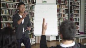 Jonge Aziatische mens met een flipchart die een lezing in bibliotheek geven stock video