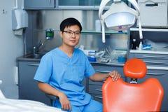 Jonge Aziatische mensentandarts met tandartsstoel bij de kliniek Dentis stock afbeelding