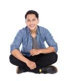 Jonge Aziatische mensenzitting op de vloer, glimlach royalty-vrije stock foto's