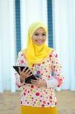 Jonge Aziatische moslimvrouw in hoofdsjaal met mobiele laptop Stock Foto