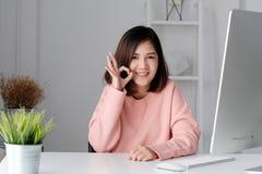 Jonge Aziatische onderneemster die het o.k. teken van het handgebaar en KMIO tonen royalty-vrije stock foto's