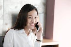 Jonge Aziatische onderneemster die slimme telefoon spreken die met gelukkig glimlachen Stock Foto's