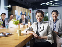 Jonge Aziatische ondernemers die in bureau samenkomen Royalty-vrije Stock Foto's