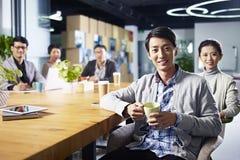 Jonge Aziatische ondernemers die in bureau samenkomen Stock Foto's