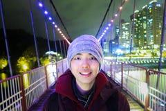 Jonge Aziatische persoon die met de zachte achtergrond van de nachtstad glimlachen stock foto