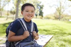 Jonge Aziatische schooljongen die met rugzak aan camera glimlachen royalty-vrije stock fotografie