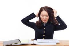 Jonge Aziatische student die probleem op bureau hebben. Stock Afbeelding