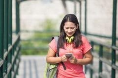 Jonge Aziatische student in haar openluchtactiviteit, die terwijl horloge lopen Stock Fotografie