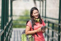 Jonge Aziatische student in haar openluchtactiviteit, die terwijl horloge lopen Stock Afbeeldingen