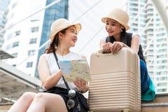 Jonge Aziatische toeristenvrouwen die hoeden dragen die richting van een kaart met het glimlachen gezichten zoeken stock afbeeldingen