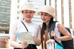 Jonge Aziatische toeristenvrouwen die hoeden dragen die richting van een kaart met het glimlachen gezichten zoeken royalty-vrije stock afbeelding
