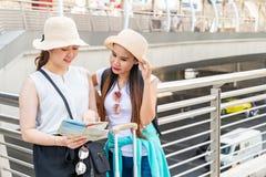 Jonge Aziatische toeristenvrouwen die hoeden dragen die richting van een kaart met het glimlachen gezichten zoeken royalty-vrije stock fotografie