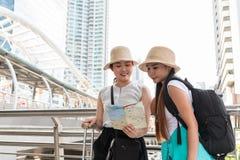 Jonge Aziatische toeristenvrouwen die hoeden dragen die richting van een kaart met het glimlachen gezichten zoeken stock foto's