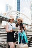 Jonge Aziatische toeristenvrouwen die hoeden dragen die richting van een kaart met het glimlachen gezichten zoeken royalty-vrije stock foto
