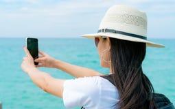 Jonge Aziatische van de de slijtagehoed van de backpackervrouw het gebruikssmartphone die selfie bij pijler nemen De zomervakanti stock afbeelding