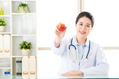 Jonge Aziatische voedingsdeskundige die een appel houden Stock Foto