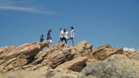 Jonge Aziatische volwassenen bovenop rotsen door het overzees stock footage
