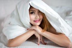 Jonge Aziatische vrouw in bed Stock Afbeelding
