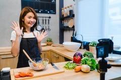 Jonge Aziatische vrouw in de video van de keukenopname op camera Glimlachende Aziatische vrouw die aan voedsel blogger concept we stock afbeelding