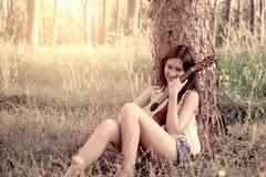 Jonge Aziatische vrouw die akoestische guitalele spelen stock afbeeldingen
