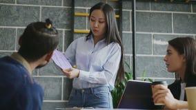 Jonge Aziatische vrouw die document architecturaal plan van huis voorleggen aan medewerkers in modern startbureau stock footage