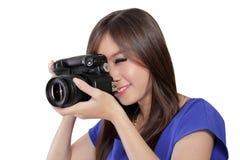 Jonge Aziatische vrouw die door beeldzoeker van digitale camera kijken Stock Afbeelding