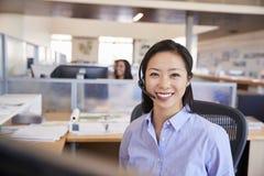 Jonge Aziatische vrouw die in een call centre werken die aan camera glimlachen royalty-vrije stock foto
