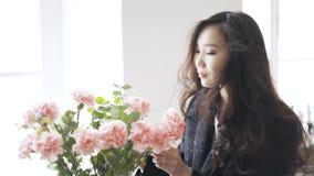 Jonge Aziatische vrouw die een roze bloem in een vaas thuis ruiken stock videobeelden