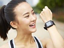 Jonge Aziatische vrouw die een vraag beantwoorden die wearable apparaat met behulp van royalty-vrije stock fotografie