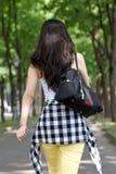 Jonge Aziatische vrouw die, foto van het achtergedeelte loopt. stock fotografie