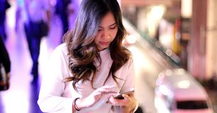 Jonge Aziatische vrouw die haar mobiele telefoon met behulp van stock foto