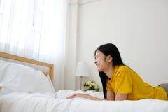 Jonge Aziatische vrouw die laptop computerzitting voor witte bakstenen muurachtergrond gebruiken met exemplaarruimte, mensen en t stock fotografie