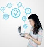 Jonge Aziatische vrouw die laptop met technologiepictogrammen met behulp van Royalty-vrije Stock Foto