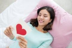 Jonge Aziatische vrouw die op bed liggen, die groetkaart met rood h houden Royalty-vrije Stock Fotografie