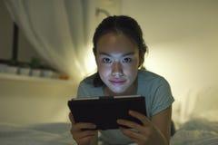 Jonge Aziatische vrouw die op bed liggen en digitale tablet gebruiken Stock Foto's