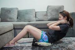 Jonge Aziatische vrouw die thuis uitwerken Stock Foto's