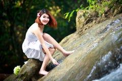 Jonge Aziatische vrouw die van de zuivere wateren van een bergrivier i genieten stock foto
