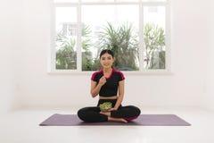 Jonge Aziatische vrouw in geschiktheidsslijtage, met vegetarische gezonde salade, die op vloer, tegen witte muur zitten royalty-vrije stock afbeeldingen