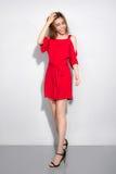 Jonge Aziatische vrouw in het rode kleding stellen dichtbij witte muur stock afbeeldingen