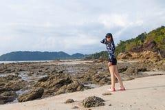 Jonge Aziatische vrouw in het zwemmen kostuum het ontspannen op zandstrand in de zomervakantie royalty-vrije stock fotografie